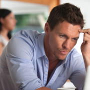 Upset man looking at a computer screen with woman in background